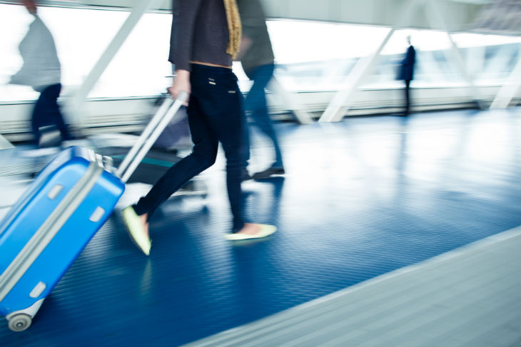 Woman rushing with suitcase at airport